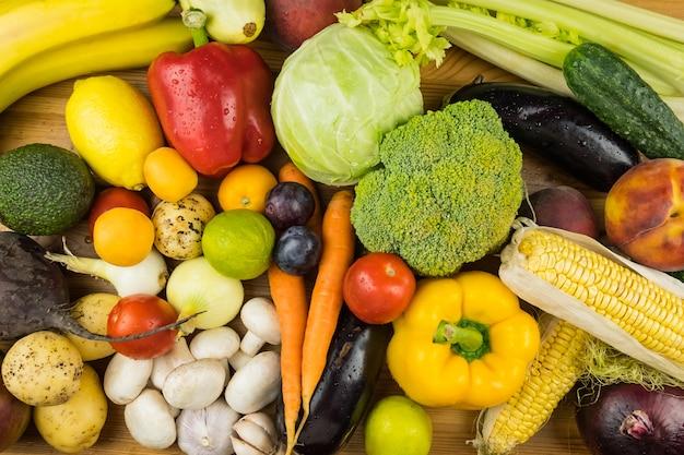 新鮮な有機野菜や果物のクローズアップのトップビューイメージ。地元産のピーマン、トウモロコシ、ニンジン、マッシュルーム、その他の自然菜食主義者向け食品をテーブルの上に置きます。
