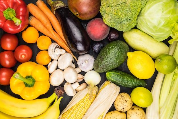 新鮮な有機野菜や果物のクローズアップのトップビューイメージ。地元で栽培されたピーマン、トウモロコシ、ニンジン、キノコ、その他の自然なビーガンフードを黒の素朴なテーブルの上に置きます。