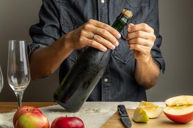 Мужские руки открывая бутылку премиум сидра. откупоривая красивую ледяную бутылку яблочного вина