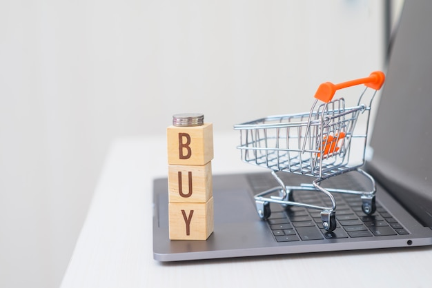 木製キューブブロックは、ミニショッピングカートとラップトップ上の単語を購入します