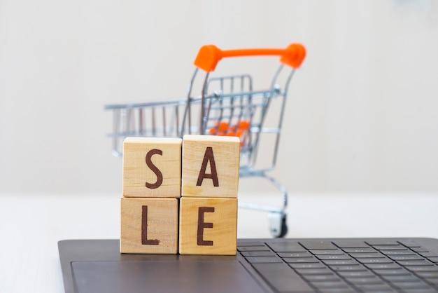 Деревянное слово продажи блока куба на компьтер-книжке с мини магазинной тележкаой.