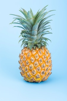 青に分離された黄色のパイナップル。創造的なトロピカルフルーツのコンセプト