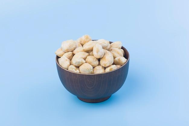 青色の背景に木製のボウルにキャンドルナッツスパイス