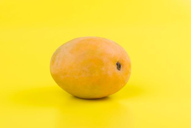 黄色の背景にオレンジのマンゴー
