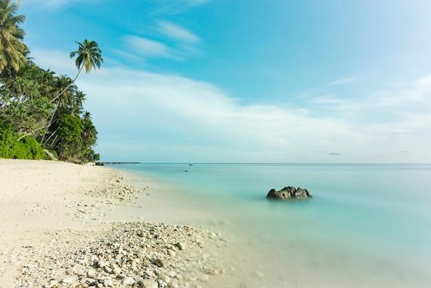 Долгая выдержка красивого вида на пляже, белом песке, кокосовой пальме и красивом голубом небе