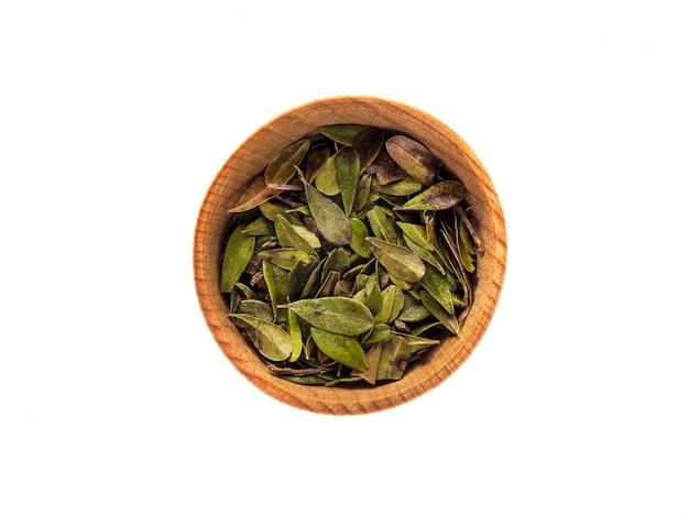 白いテーブルの上の木製カップでアルクトスタフィロスの乾燥した葉