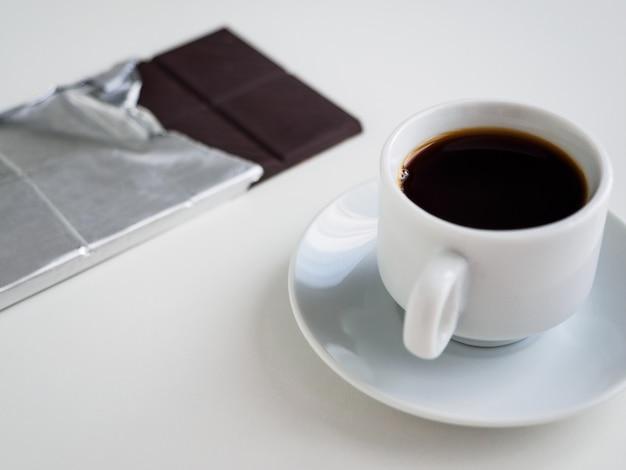 一杯のブラックコーヒーとホイルのダークチョコレート