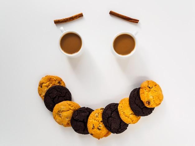 Улыбка на столе с кофе, печеньем и корицей