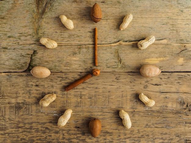 さまざまなナッツとシナモンの木製テーブルで作られた時計