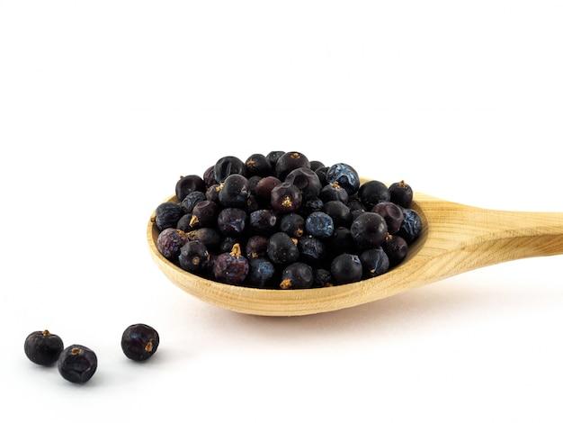 Сухие ягоды можжевельника лежат в деревянной ложке на белом