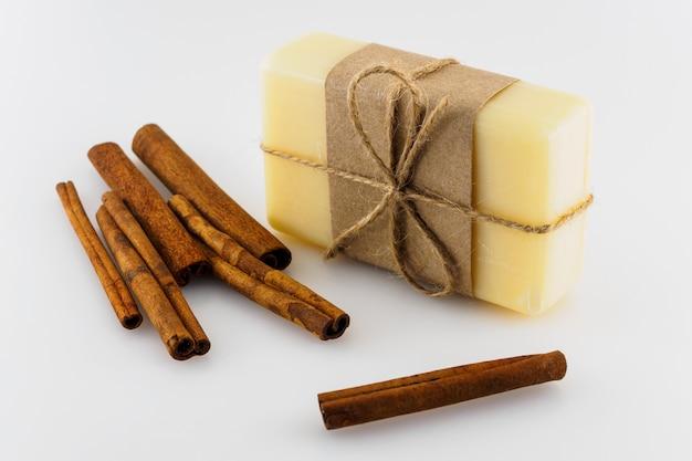 白い背景の上の黄色の手作り石鹸とシナモンの棒。