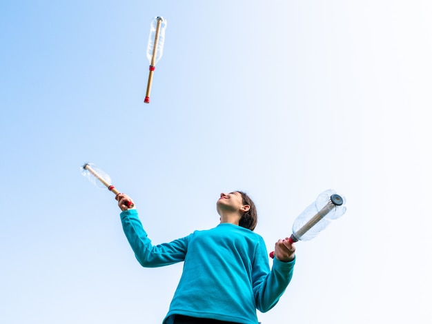 Девочка-подросток жонглирует бутылками в саду
