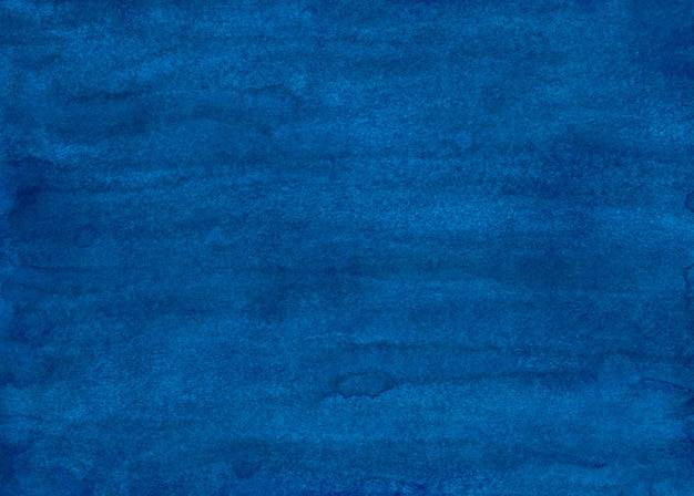 水彩の深い青色の背景の絵。手描きの水彩画。紙のテクスチャの汚れ。