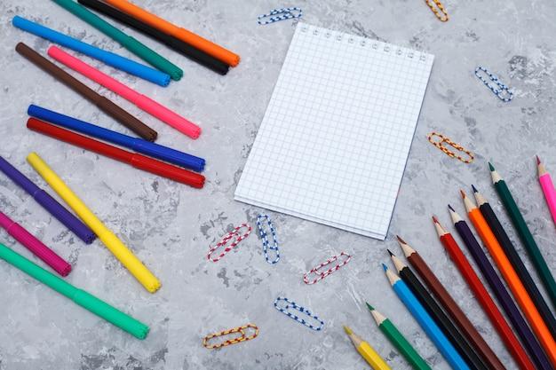 色鉛筆、フェルトペン、白いシート、ペーパークリップはグレーの上にあります