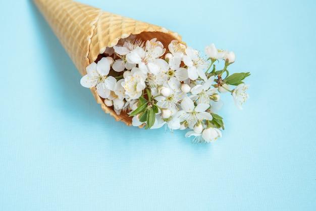 青色の背景に白い花を持つアイスクリームコーン。最小限の春のコンセプト。フラット横たわっていた、花の背景。テキスト用のスペース