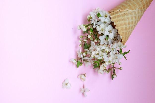 ピンクの背景の白い花を持つアイスクリームコーン。春のコンセプトです。花の背景。フラット横たわっていた。テキストのためのスペース