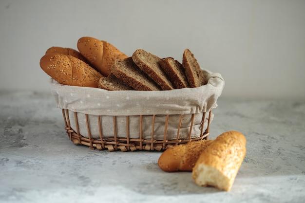 ゴマとライ麦パンのスライスを入れた焼きたてのパンのバゲットは、テーブルのブレッドボックスにあります。ベーカリー。フラット横たわっていた。クローズアップ、ミニマリズム。