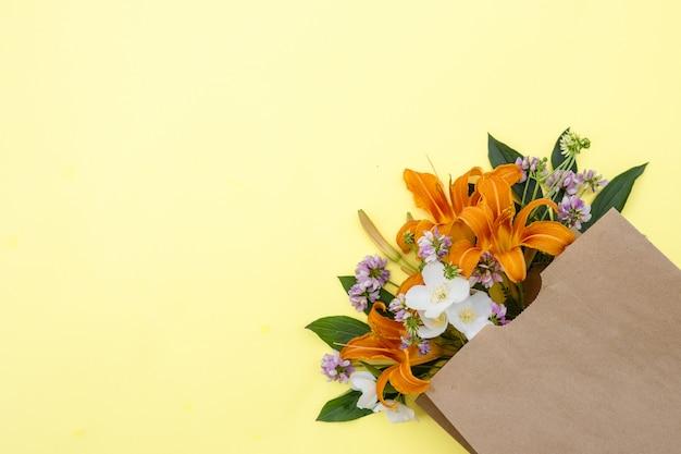 黄色の背景にクラフトバッグのユリの花の花束