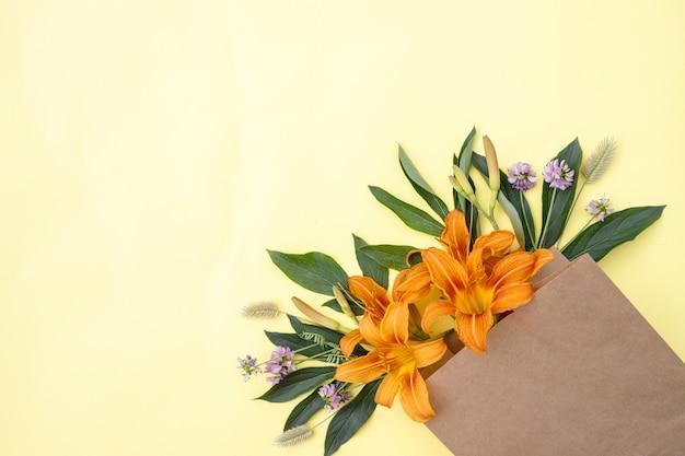 黄色の背景にクラフトバッグにユリの花の花束。花の配達。花の組成物。テキストのためのスペース。春の背景。フラット横たわっていた。植物相。休日のはがき。