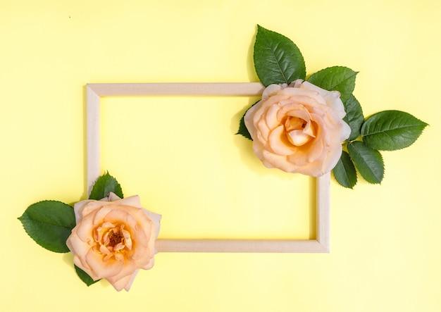 花の組成物。黄色い背景、テキスト用のスペースに自然なバラの花と緑の葉のフレーム。春の背景。フラット横たわっていた。