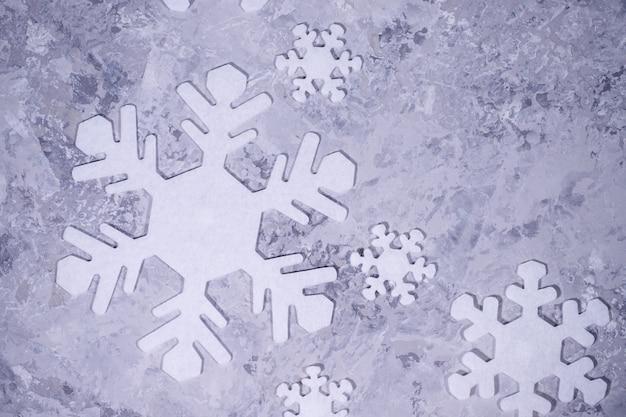 Рождество, зима, новый год концепция. серый фон с белыми снежинками. плоская планировка, вид сверху