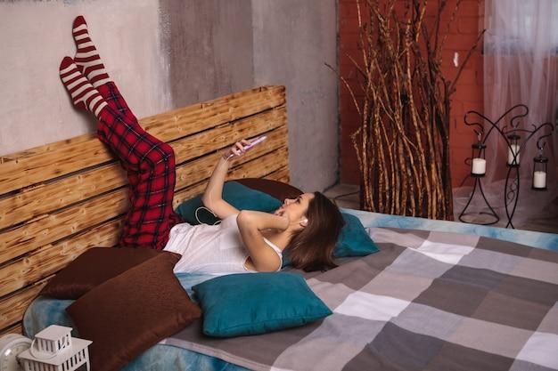 ヘッドフォンと携帯電話を手にした若い女性が、足を上にしてベッドに横たわっています。女の子が電話で自分の写真を撮ります。