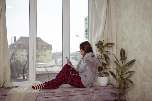 Девочка-подросток сидит на окне с телефоном в руке и слушает что-то в наушниках. одиночество. молодая женщина смотрит в окно