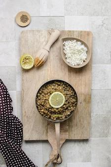 木製のまな板の上にレンズ豆のボウルとご飯の小さなボウル