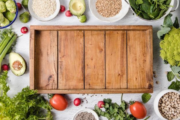 白い表面と空の木製トレイの上に置かれた季節の野菜と全粒穀物の品揃え