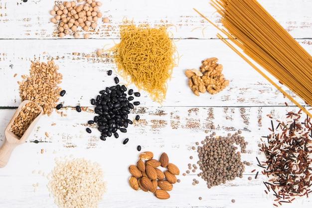 別の種類の全体のスパゲッティと全粒穀物が白いテーブルの山に配置