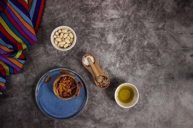 真ん中に配置された黒板にメキシコ料理を準備するためのツリーレッドチリス、ピーナッツ、塩、コショウ、オリーブオイル