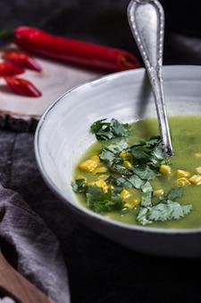 コーンとコリアンダーのトッピンと赤唐辛子の入った緑のスープのボウル