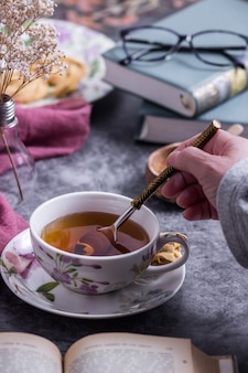 Человек помешивает чай с ложкой