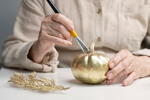 年配の女性がカボチャを塗ります。ライフスタイル年金受給者。古い手は、ブラシでゴールドペイントでカボチャをペイントします。