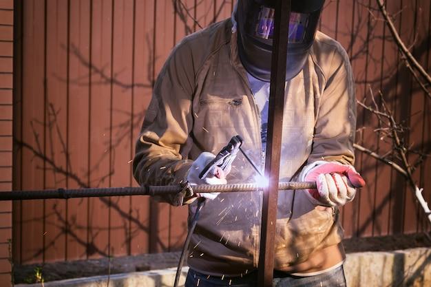 Рабочий в защитной маске сваривает металл сварочным аппаратом. профессия сварщика. работа в саду