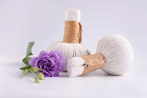 ハーブの袋と白い表面に紫の花でマッサージするための化粧品セット