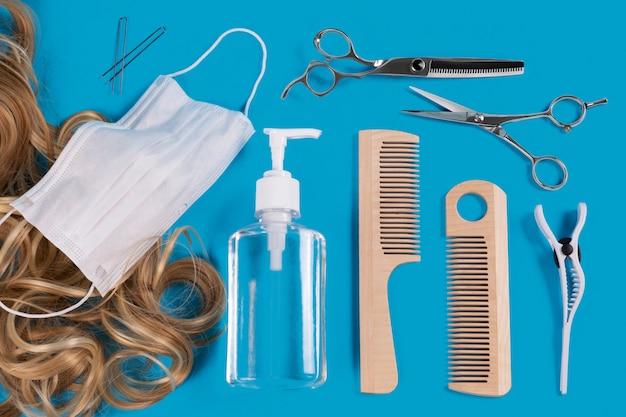 長いブロンドの髪はさみと櫛で青い表面に理髪セット