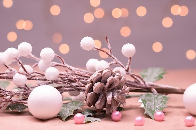 Рождественская открытка в розовых тонах. рождественская веточка с шишкой, шарами и огнями