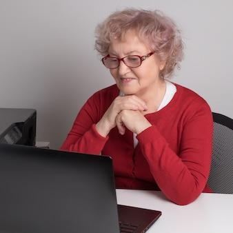 Пожилая женщина работает с ноутбуком на белом столе.