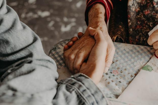 親切。古い手が若い手を握って。