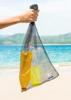 ビーチからプラスチックを拾うリサイクル