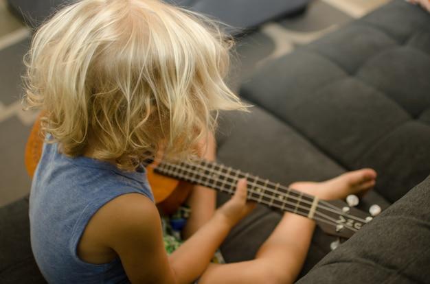 Малыш учится играть на деревянной гавайской гитаре.