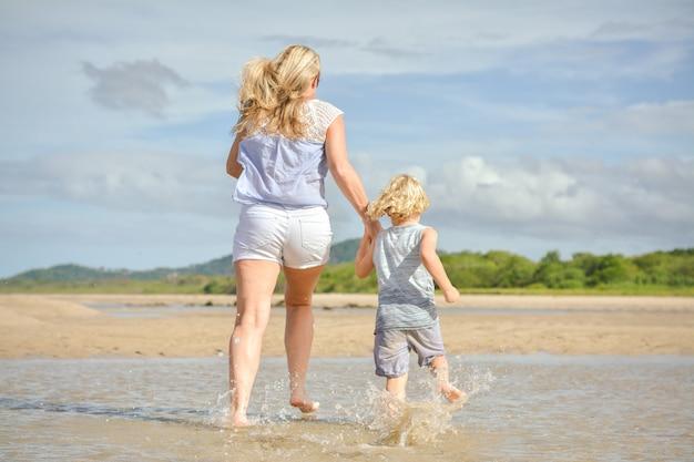 母とビーチで走っている息子
