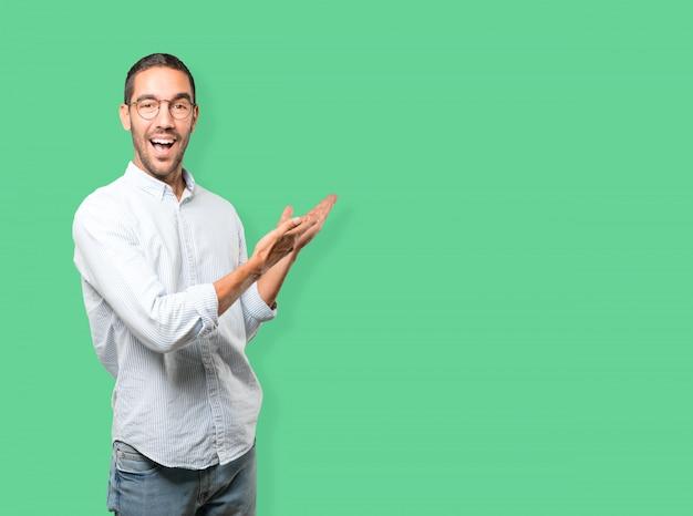 歓迎のジェスチャーを作る驚いた若い男