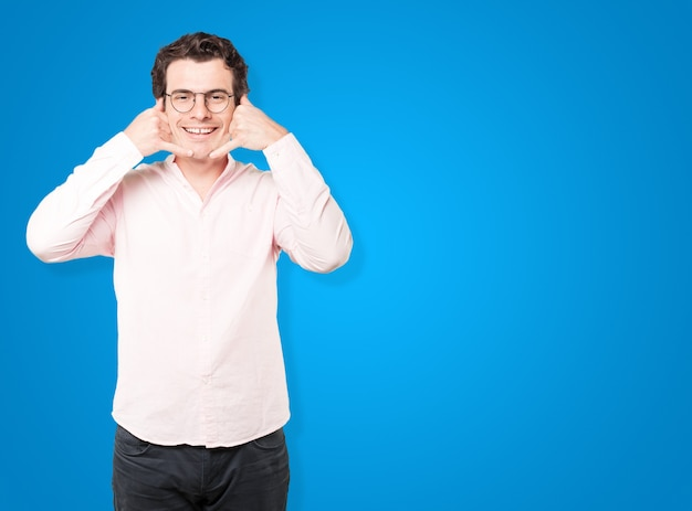 Счастливый молодой человек, делая жест вызова рукой