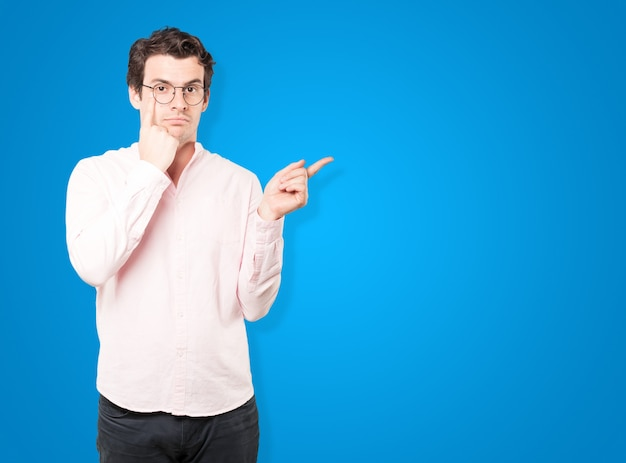 彼の手が彼の目を指していると注意するジェスチャーをするためらう若い男