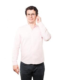 Обеспокоенный молодой человек переживает из-за громких шумов и прикрывает уши