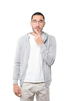 Сконцентрированный молодой человек делает жест недоверия