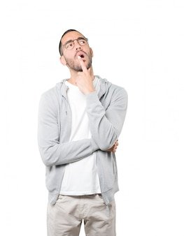 Удивленный молодой человек делает жест сомнения
