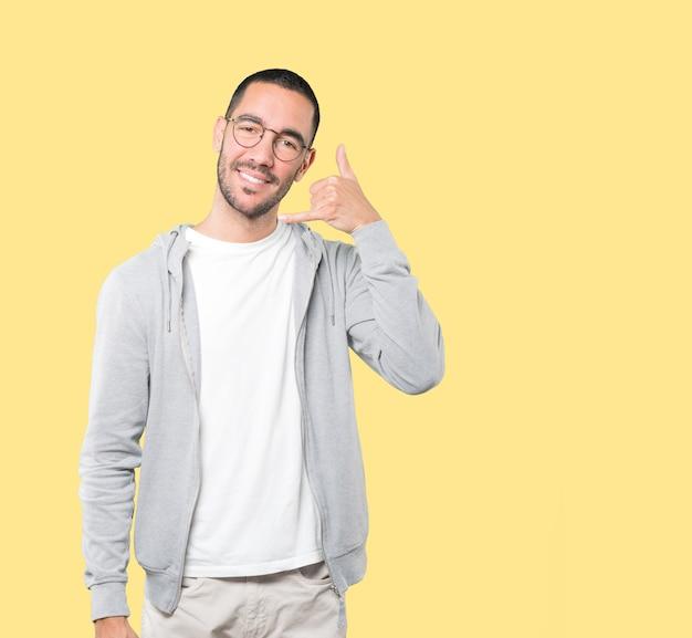 手で呼び出すのジェスチャーを作る幸せな若い男